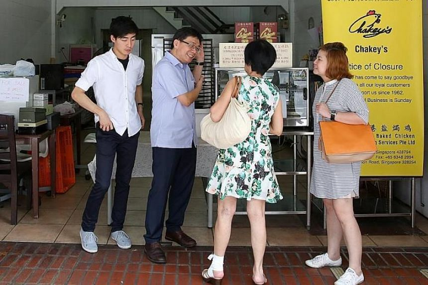 (From left) Mr Samuel Chak and his father Richard with customers.