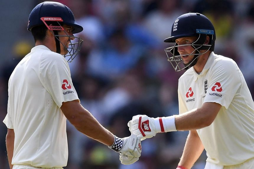 England's batsman Alastair Cook (left) and teammate Joe Root bump fists during their partnership against Australia on the second day of the fourth Ashes cricket Test match at the MCG in Melbourne on Dec 27, 2017.