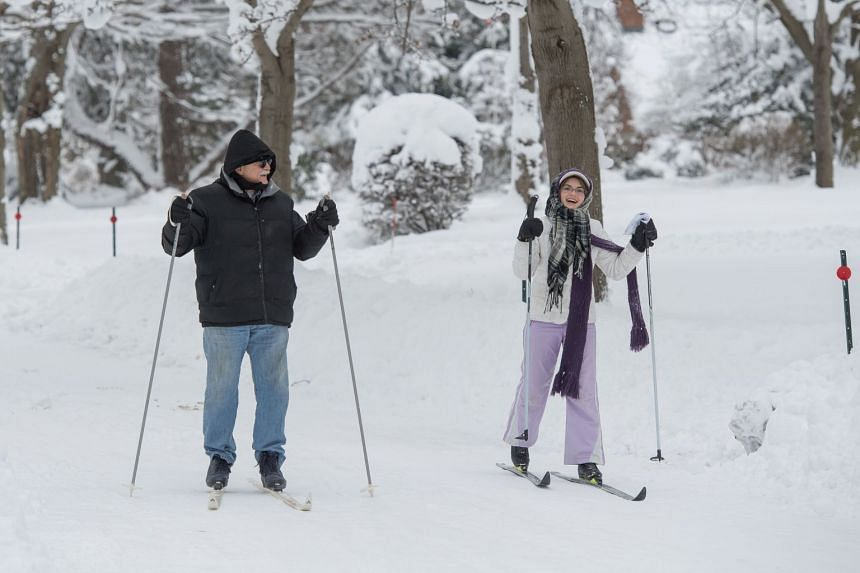 Joe Ferrera and Grace Ferrera cross country ski on South Shore Drive after two days of record-breaking snowfall in Erie, Pennsylvania, US, on Dec 27, 2017.