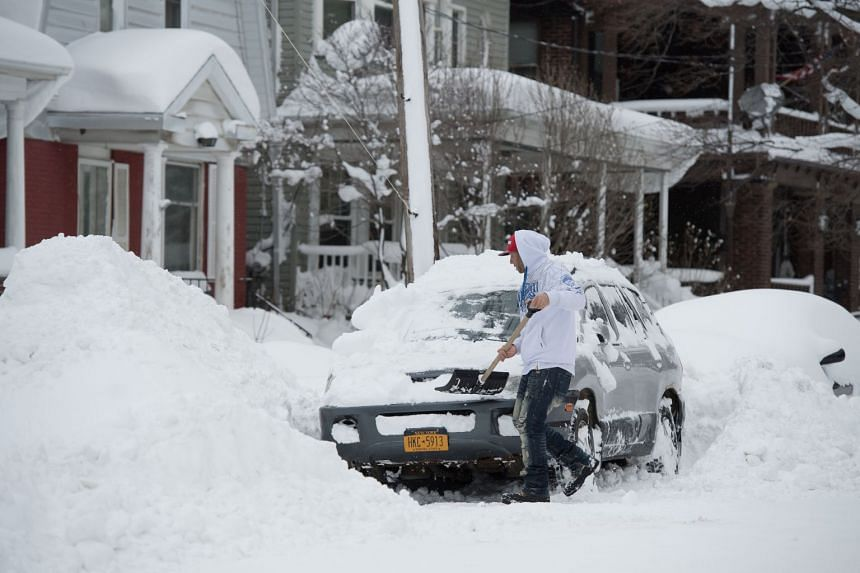 A man removes snow from his vehicle after two days of record-breaking snowfall in Erie, Pennsylvania, US, on Dec 27, 2017.