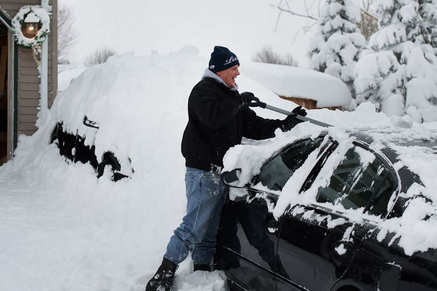 Jeff Strum removes snow off of his car after two days of record-breaking snowfall in Erie, Pennsylvania, US, on Dec 27, 2017.