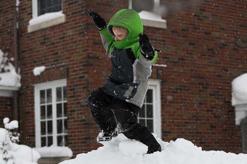 Silas Stueve plays in the snow after two days of record-breaking snowfall in Erie, Pennsylvania, US, on Dec 27, 2017.
