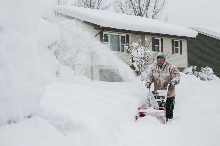 Thomas Berry removes snow from the sidewalk in front of his home after two days of record-breaking snowfall in Erie, Pennsylvania, US, on Dec 27, 2017.