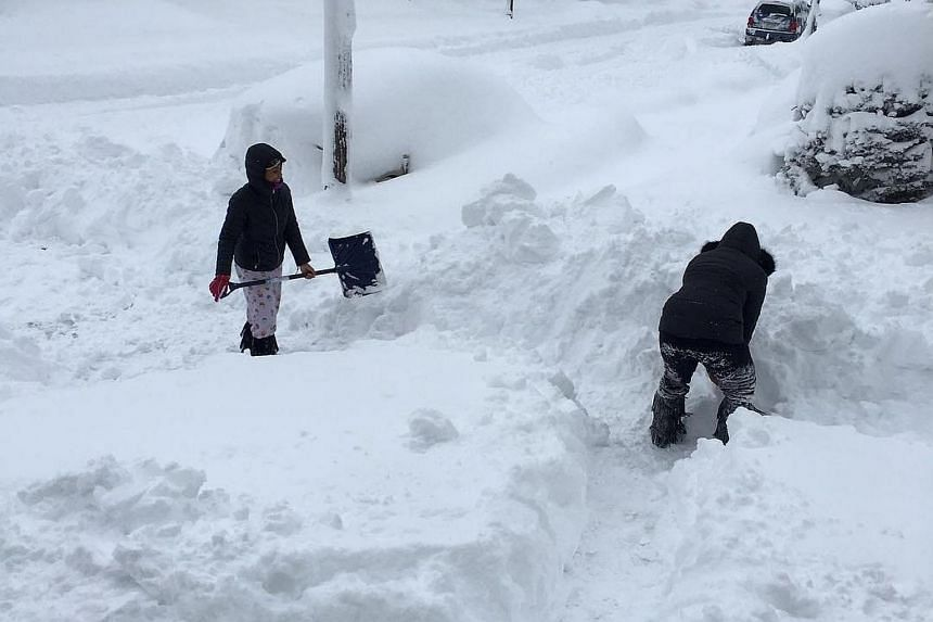 People dig out the path by their house after the record snowfall in Erie, US, on Dec 26, 2017.