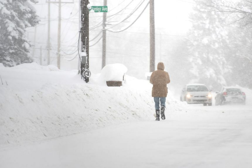 A resident walks north on Pine Ave as more snow falls after two days of record-breaking snowfall in Erie, Pennsylvania, US, on Dec 27, 2017.