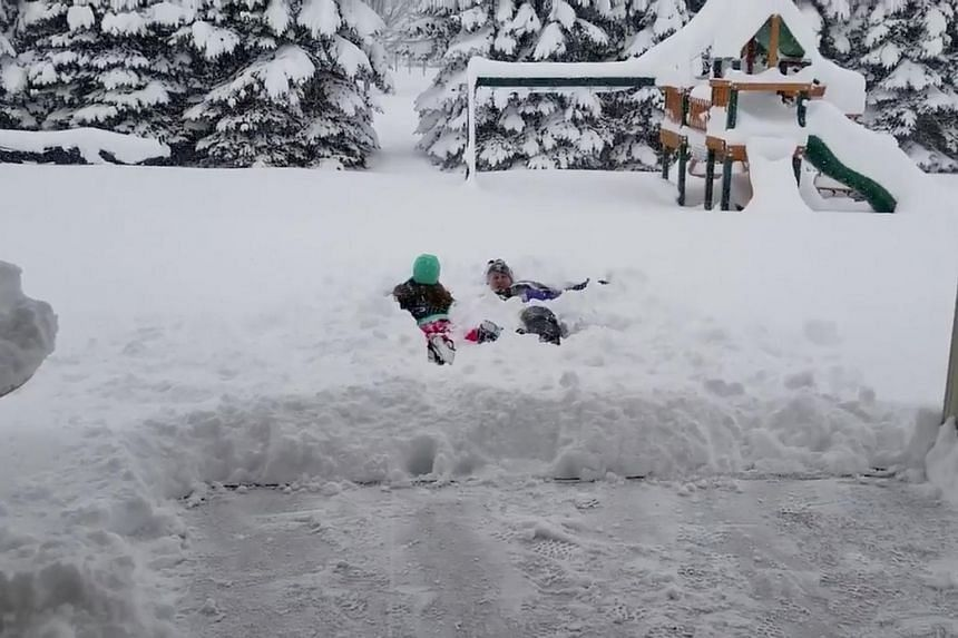 People are seen lying in the snow after the record snowfall in Erie, Pennsylvania, US, on Dec 26, 2017 in this picture obtained from social media video.