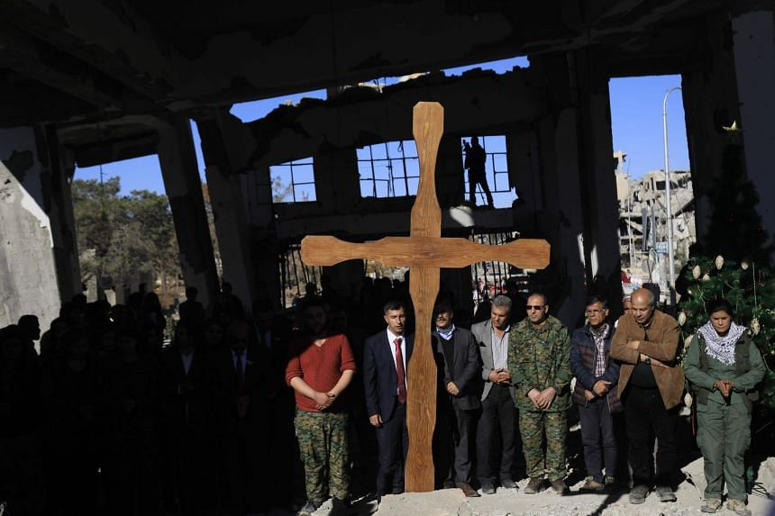 Members of the Syriac Military Council and members and leaderships of the Arab-Kurdish Syrian Democratic Forces take part in a Christmas celebration at the heavily-damaged Armenian Catholic Church of the Martyrs.