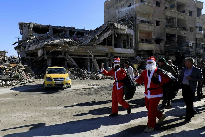 Men dressed as Santa Claus walk past destroyed buildings in the eastern Syrian city of Raqa.