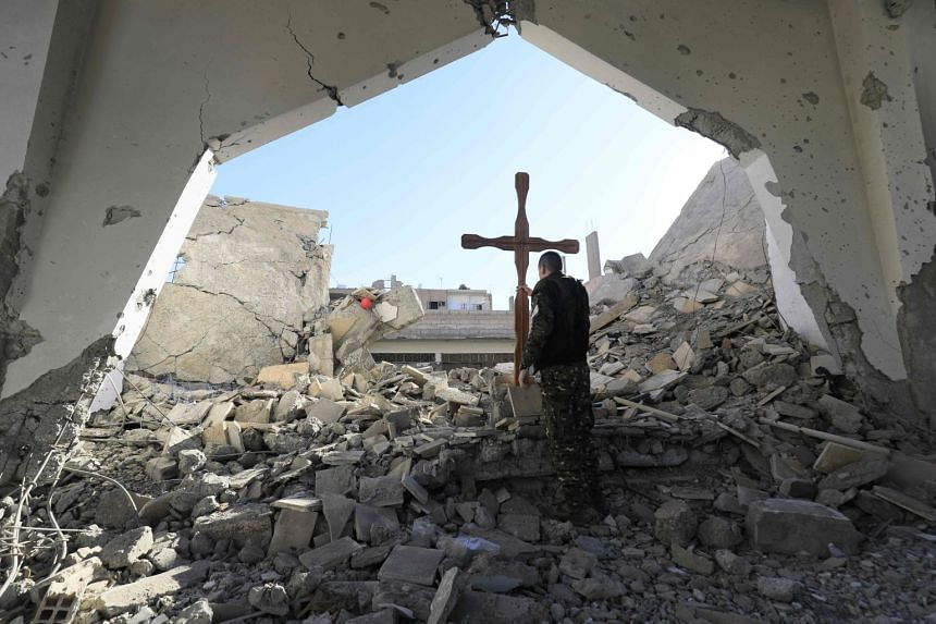 A member of the Syrian Arab-Kurdish forces places a cross in the rubble ahead of a Christmas celebration at the heavily-damaged Armenian Catholic Church of the Martyrs.