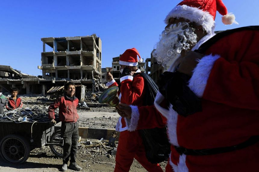 A Syrian child smiles as men dressed as Santa Claus walk past destroyed buildings in Raqa.