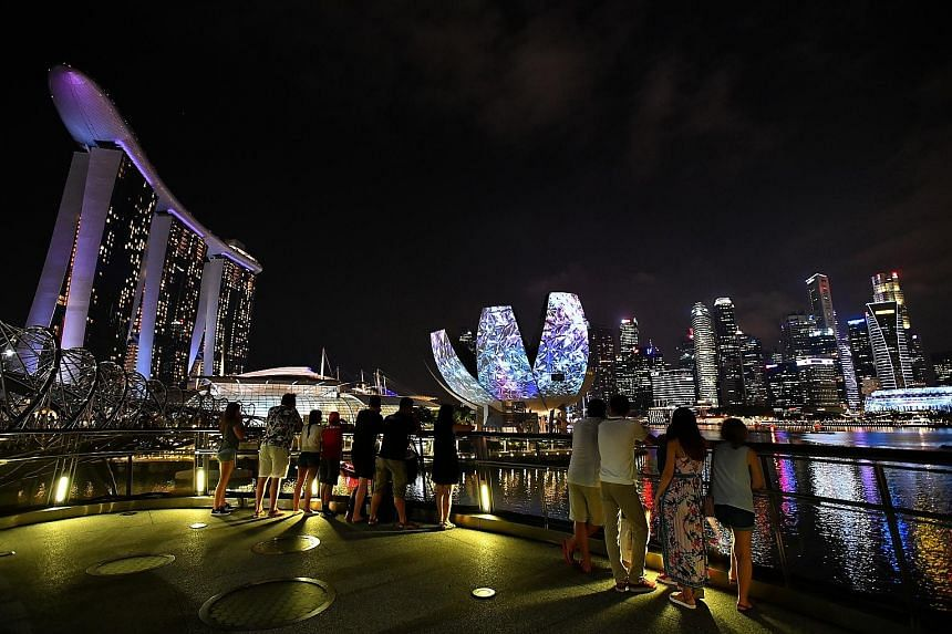 Mr Michael Rush, surprised Ms Andrea Singco at the Merlion Park last night by going down on one knee and proposing to her as bursts of colourful lights brightened the night sky and facades of the Merlion and ArtScience Museum. Light projections on th