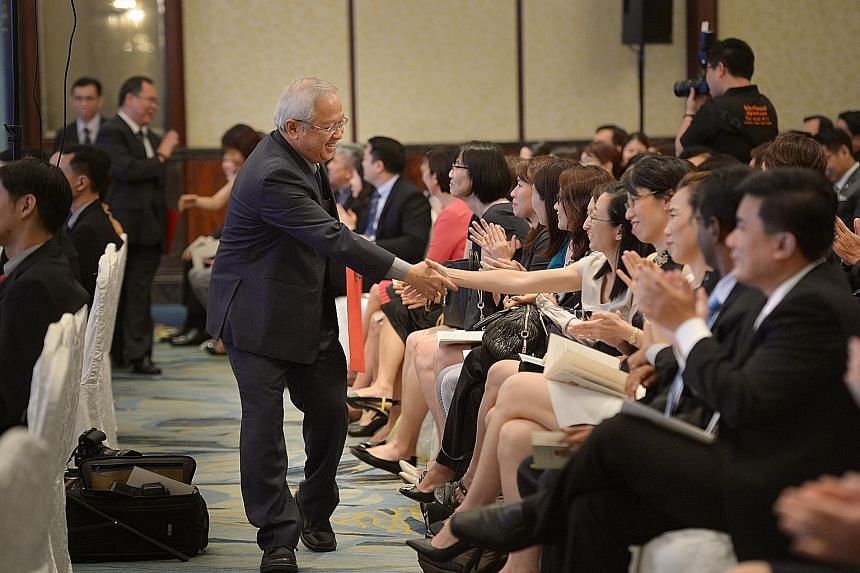 Dr Hon Chiew Weng, the retiring principal of Hwa Chong Institution, being greeted by colleagues after receiving his certificate at the Appointment and Appreciation Ceremony for Principals at the Shangri-La Hotel yesterday. Sixty-three principals rece