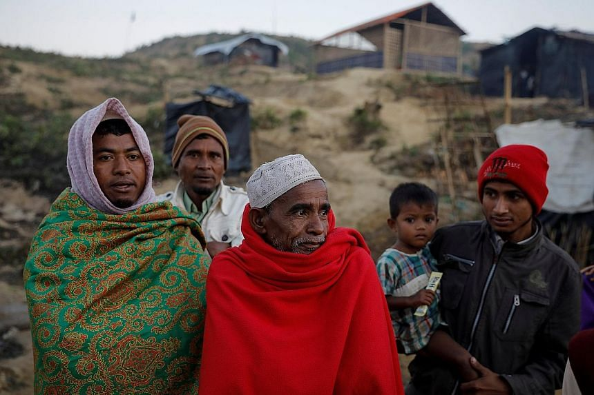 Above: Heavy snow in Beitun, in China's Xinjiang autonomous region, on Wednesday. Below: Rohingya refugees trying to stay warm at the Palongkhali refugee camp near Cox's Bazar in Bangladesh, on Sunday. In Myanmar, snow fell in the districts of Loilen
