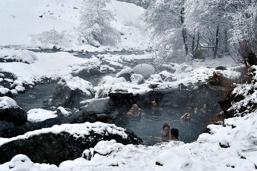 Amid the wintry chill, a child in Riedlingen, in southern Germany, enjoys a bit of fun in the snow during the festive season. Above: People braving the cold to take a dip in the natural hot water springs of Bormio, in the north of Italy, on Wednesday