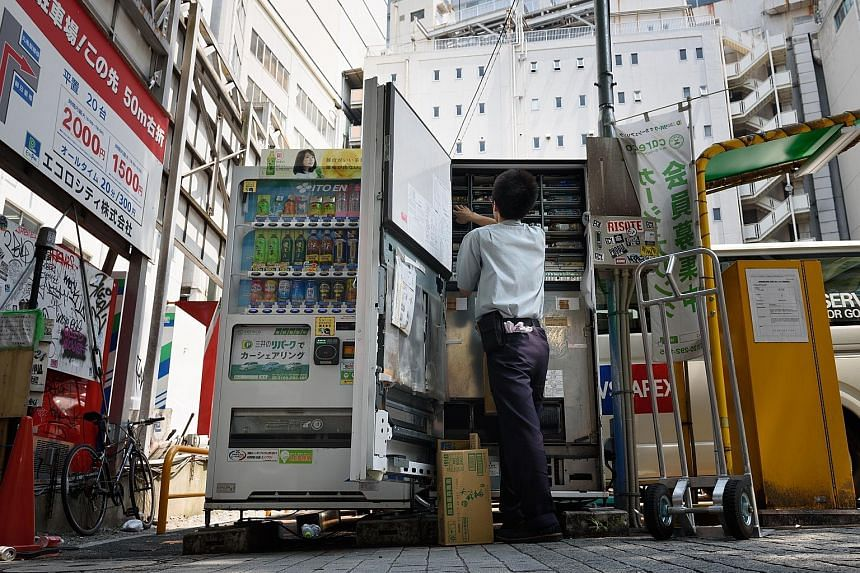 A worker filling up a vending machine. Japan's November retail sales, including food and beverage, rose 2.2 per cent from a year ago.