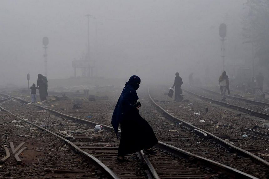 A Pakistani woman walks through dense fog across railway tracks on the outskirts of Lahore on Dec 15, 2017.