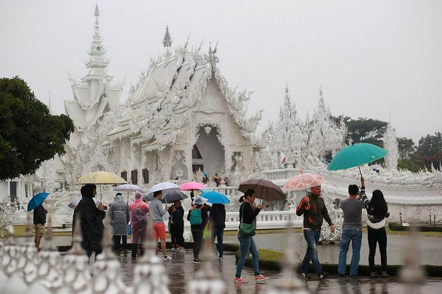Tourists flock to Wat Rong Khun in Chiang Rai province despite the rain as a cold front from China and the weakening storm Tembin continued to influence weather patterns across Thailand.