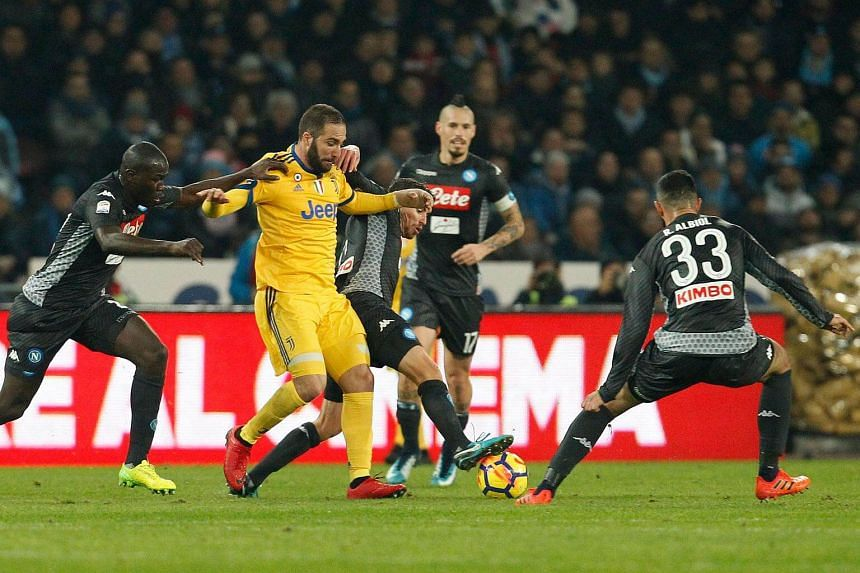 Juventus' forward Gonzalo Higuain (centre) fights for the ball with Napoli's midfielder Jorginho, Napoli's defenders Kalidou Koulibaly (left) and Raul Albiol (right) during the Italian Serie A football match between Napoli and Juventus at the San Pao