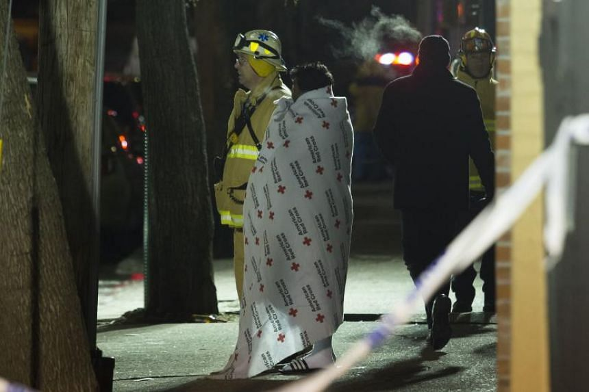 A woman covered with a Red Cross blanket talks to a fire fighter during a major house fire on Prospect avenue on Dec 28, 2017 in the Bronx borough of New York City.
