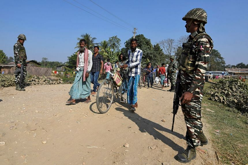 Villagers walk past Central Reserve Police Force (CRPF) personnel patrolling a road ahead of the publication of the first draft of the National Register of Citizens (NRC) in Assam, India on Dec 28, 2017.
