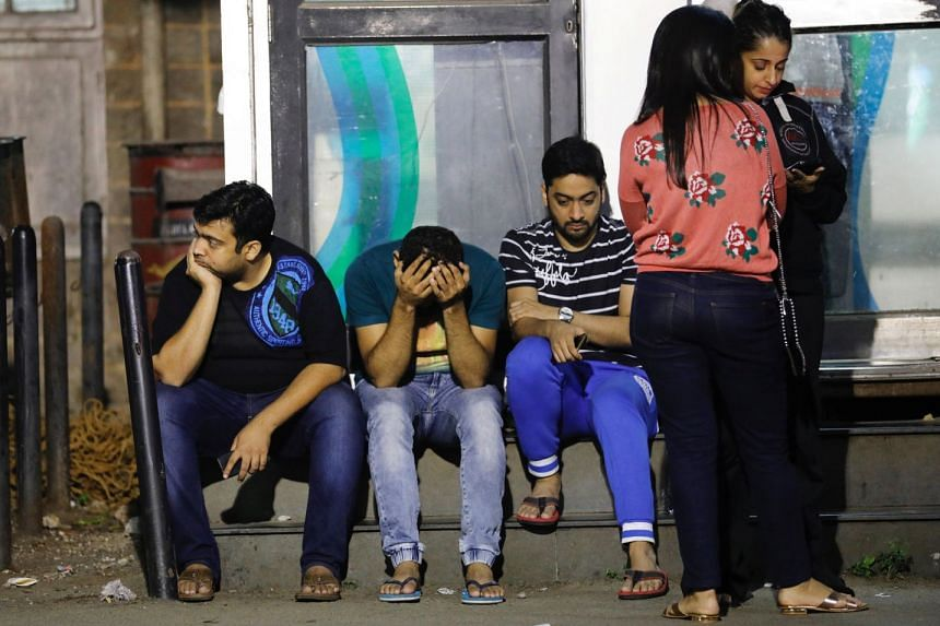 Friends of a victim killed in a fire at a restaurant wait at a hospital in Mumbai, India.