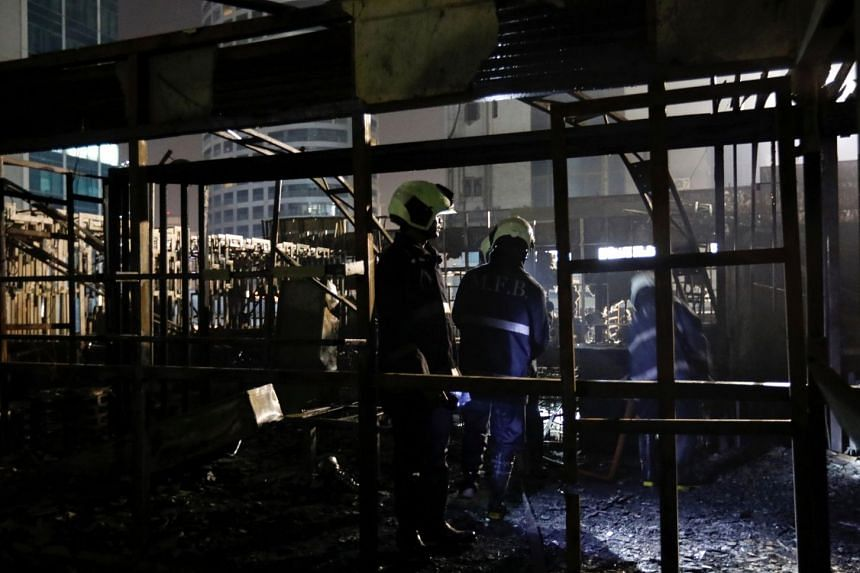 Firemen inspect the debris after a fire at a restaurant in Mumbai, India on Dec 29, 2017.