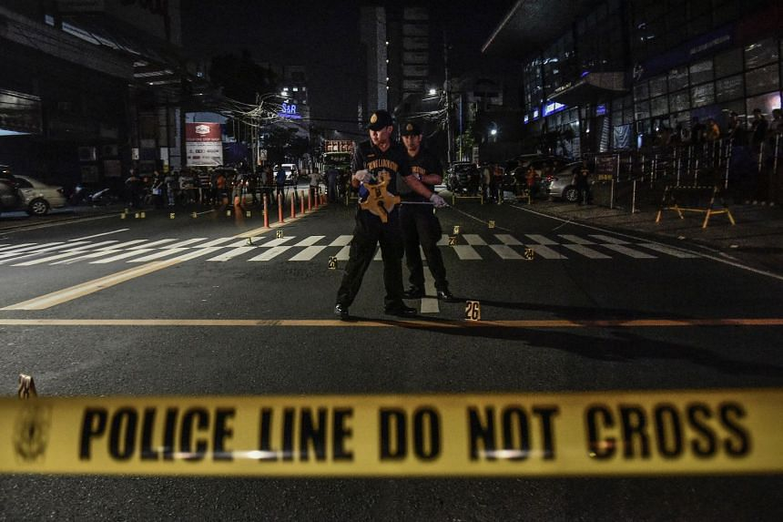 Members of the Philippine National Police's Scene of the Crime Operatives unit conduct an investigation following a police operation on a street in Mandaluyong city, Manila, on Dec 29, 2017.