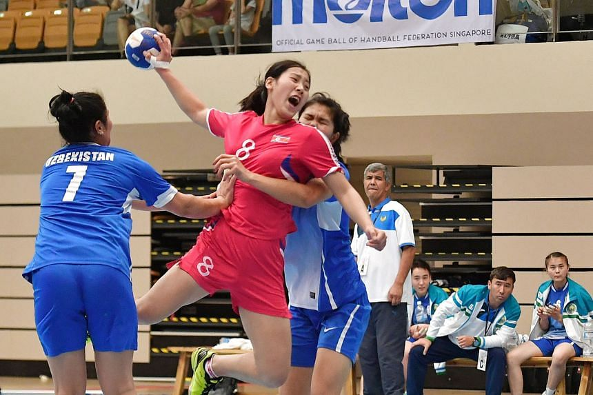 North Korea's Han Chun Yon (in red) was part of the team who beat Uzbekistan 40-25 in the women's final of the Singapore Handball Open at Our Tampines Hub yesterday. The annual Singapore Handball Open, into its fifth edition, featured 13 teams - nine