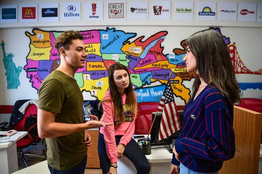 Turkish students chat in front of a US map at an education travel agency in Istanbul.