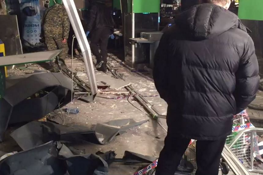 A stiil video image shows investigators working on the site of a blast at a St Petersburg supermarket.