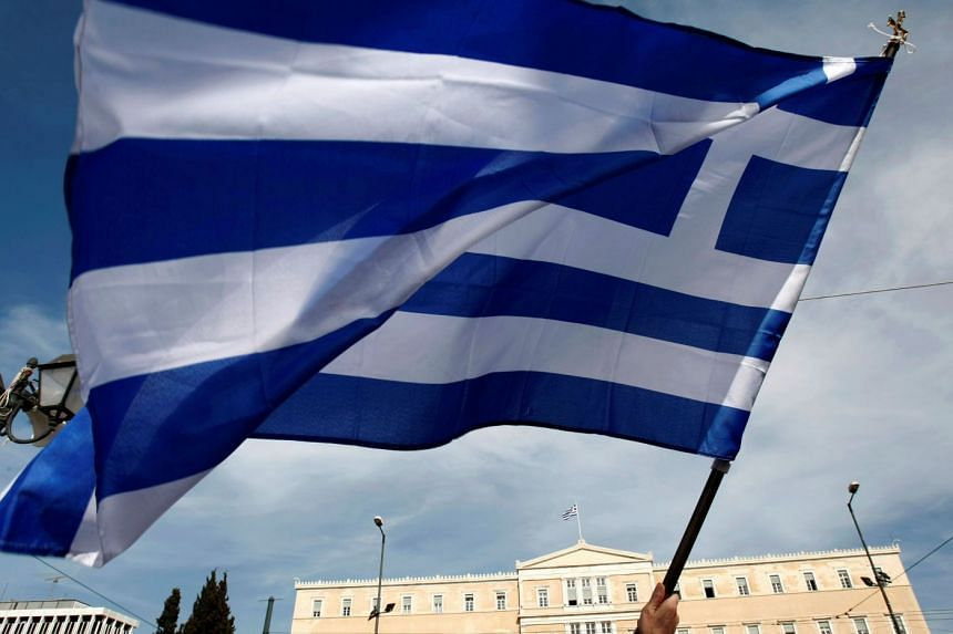 A Greek flag being waved outside the parliament building in Athens.