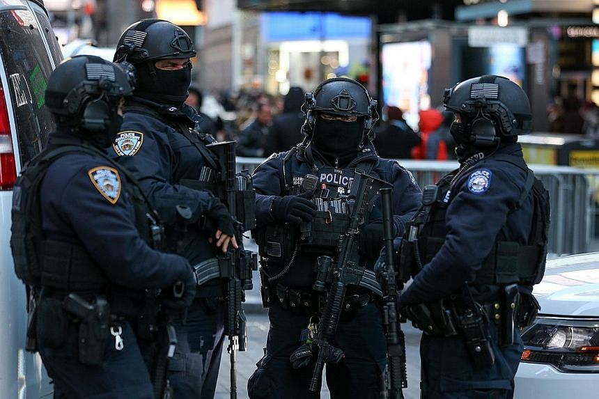 New York Police Department Counterterrorism Bureau members at Times Square on Thursday as part of beefed-up security ahead of New Year's Eve celebrations in Manhattan. Heavy-weapons teams and dog patrols will also be deployed throughout the area.