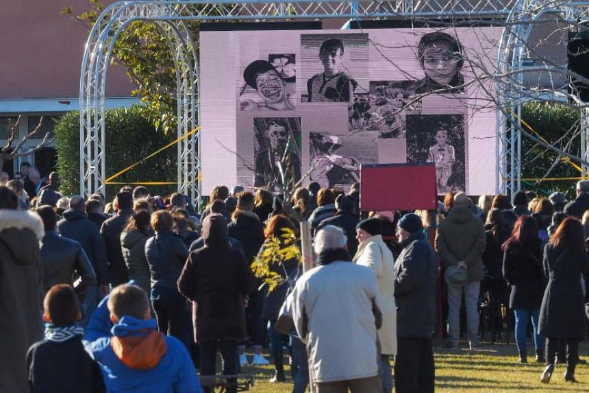 People watch a screen displaying portraits on Dec 21, 2017 in Saint-Feliu d'Avall, during the funeral ceremony for the victims of the collision between a train and a school bus in southern France which left six children dead on December 14.
