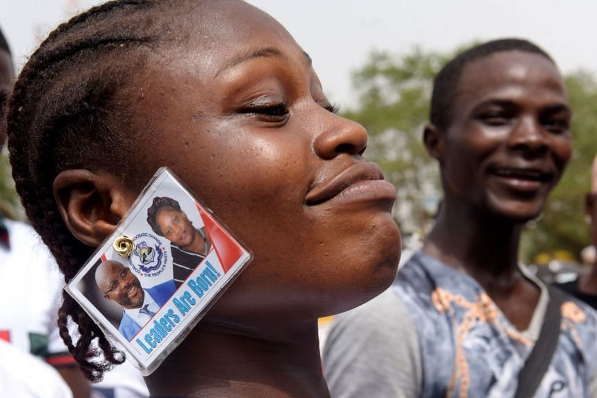 A George Weah supporter wears his image as an earring, during celebrations following his election.
