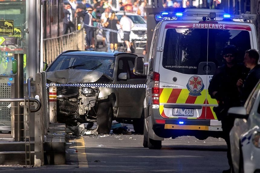 Australian police near a crashed vehicle after they arrested the driver of a vehicle that had ploughed into pedestrians at an intersection near the Flinders Street train station in central Melbourne, on Dec 21, 2017.