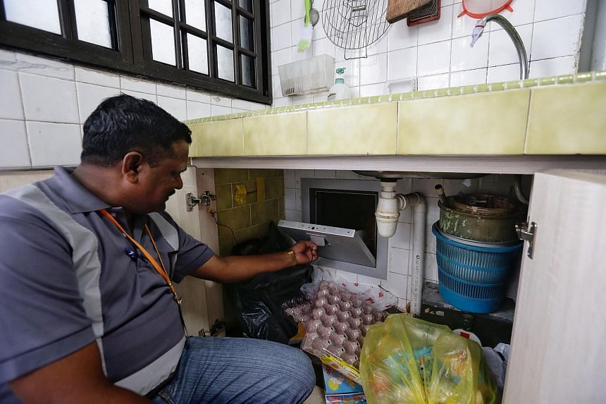 A staff member shows the new rubbish chute door of Mr Chew Ang Moh's flat.