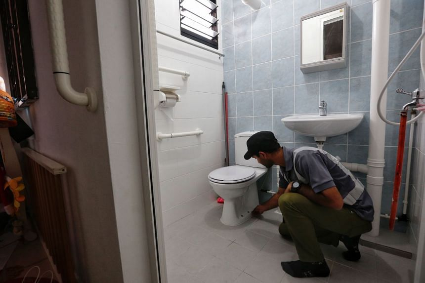 A supervisor inspects the tiles in the toilet of Ease / HIP recipient Mr Chew Ang Moh,  who had his HDB flat at Jurong West Street 41 spruced up recently.