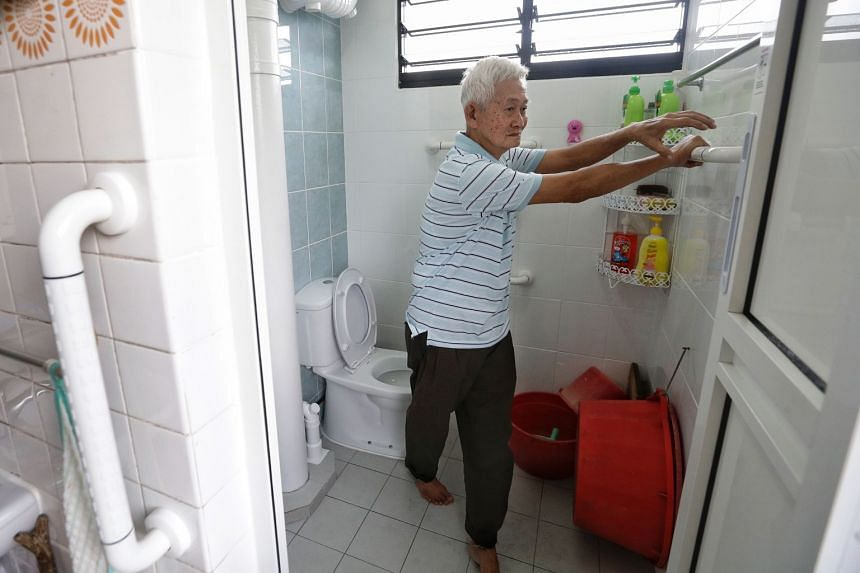 Mr Chew Ang Moh uses the newly installed grab bars in his spruced-up toilet.