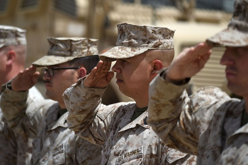 US marines salute during a handover ceremony at Leatherneck Camp in the Afghan province of Helmand.
