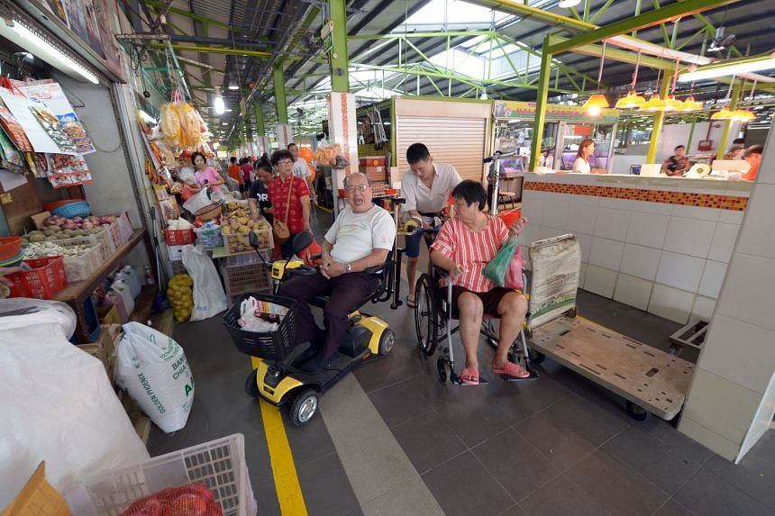 Mr Francis Tan (left), who uses a personal mobility device to get about, welcomes the wider ramps at the hawker centre.
