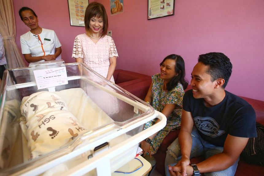 Dr Amy Khor with Ms Nabilla Hashim, 29, and Mr Fadli Bohari, 31, and the couple's first child, a baby girl. Ms Nabilla said she plans to breastfeed her daughter for the first two years.