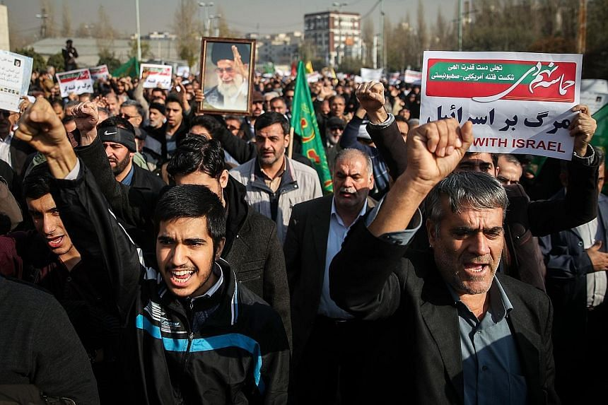 People chanting slogans in the Iranian capital Teheran as they marched in support of the government yesterday. The pro-government rallies have been held annually to mark the end of months of street protests, which followed former president Mahmoud Ah