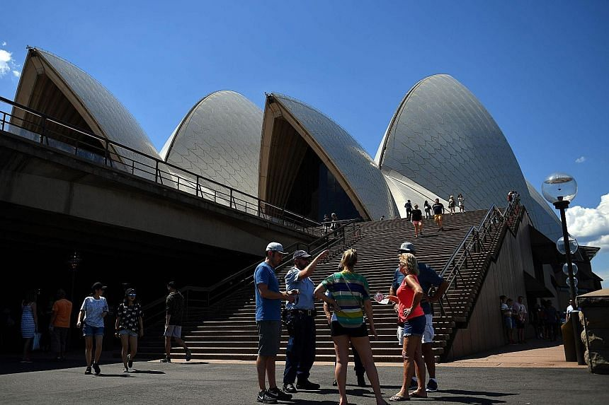A police officer providing information to visitors at the Opera House in Sydney yesterday. One million revellers are expected in the city for the countdown festivities. Members of an Indonesian anti-terror police unit taking part in a drill at the Na