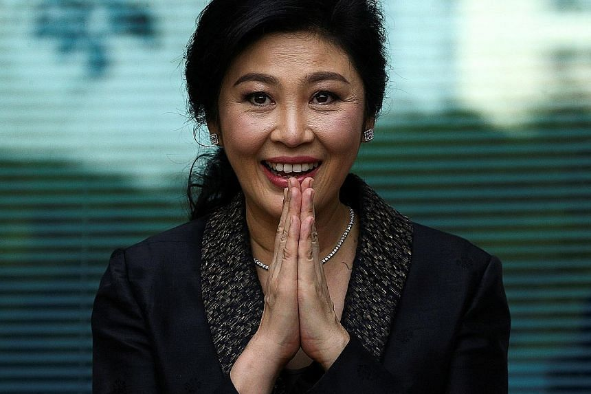 Above: A photo purportedly showing ousted former Thai prime minister Yingluck Shinawatra shopping in London. Left: Yingluck greeting supporters in Bangkok in August.