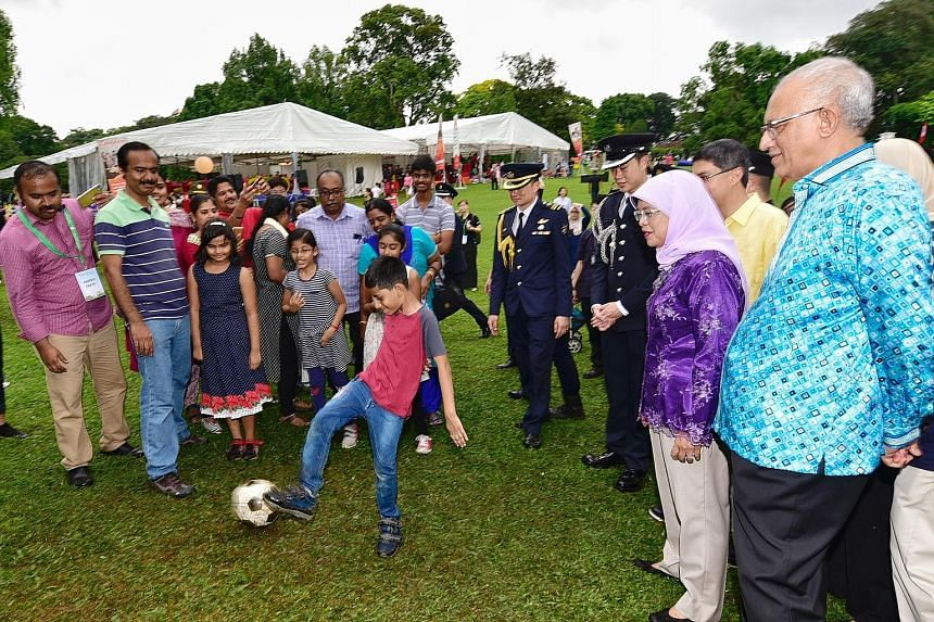 President Halimah Yacob and her husband, Mr Mohamed Abdullah Alhabshee, observing eight-year-old Adhavan Senthil Kumar kicking a football while his family members look on. The Jayabalan family - all 17 of them - was among the crowd at the Families fo