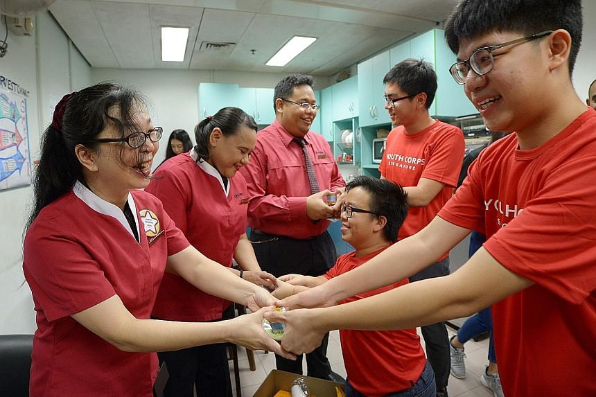 From left: SMRT staff members Hong Yoke Kee, Nurulhuda Sarbini and Muhammad Zamil receiving gifts of appreciation from volunteers Lee Ci En, Li Wee Shyan and Wong Wei Sheng.