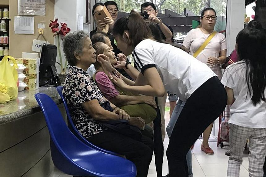 Republic Polytechnic students applying makeup on seniors before they have their portraits taken.
