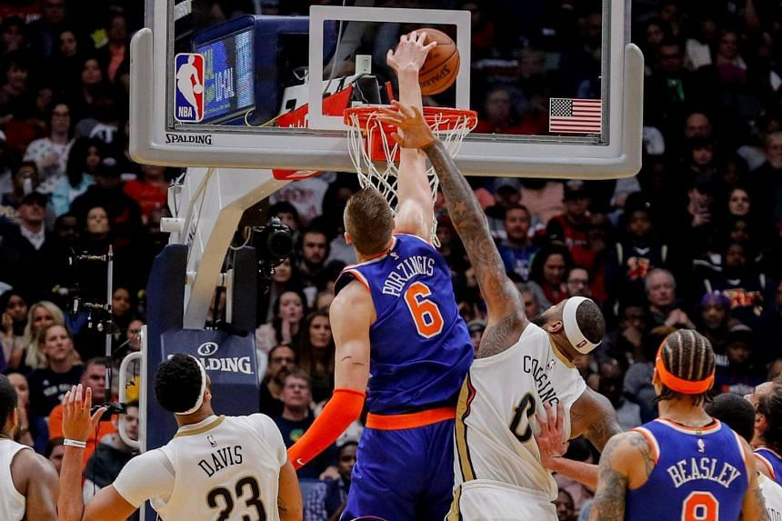 New York Knicks forward Kristaps Porzingis dunks the ball during the fourth period against New Orleans Pelicans center DeMarcus Cousins at Smoothie King Center.