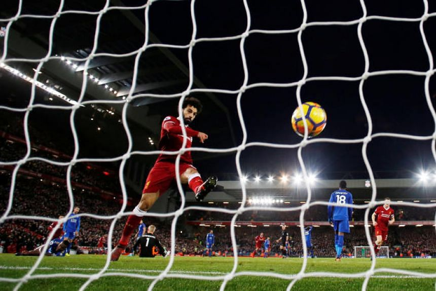 Liverpool's Mohamed Salah celebrates scoring their second goal by kicking the ball into the net.