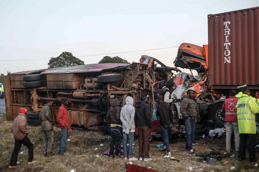 People look at the wreckage of a bus and a lorry that crashed in a head-on collision, killing thirty people, at the accident scene near Nakuru, Kenya, on Dec 31, 2017.